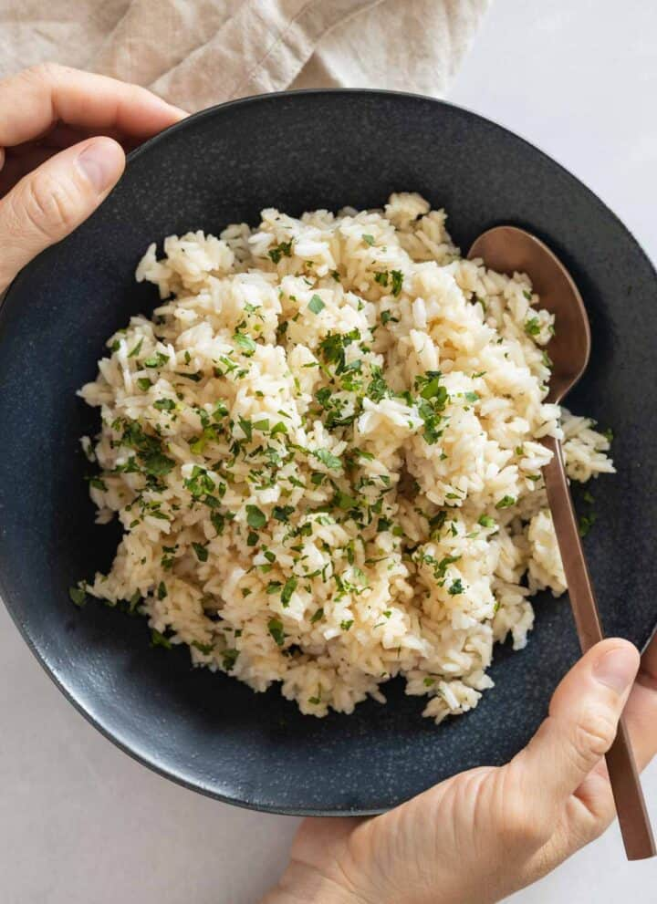 Coconut Rice in a blue bowl held in hands.