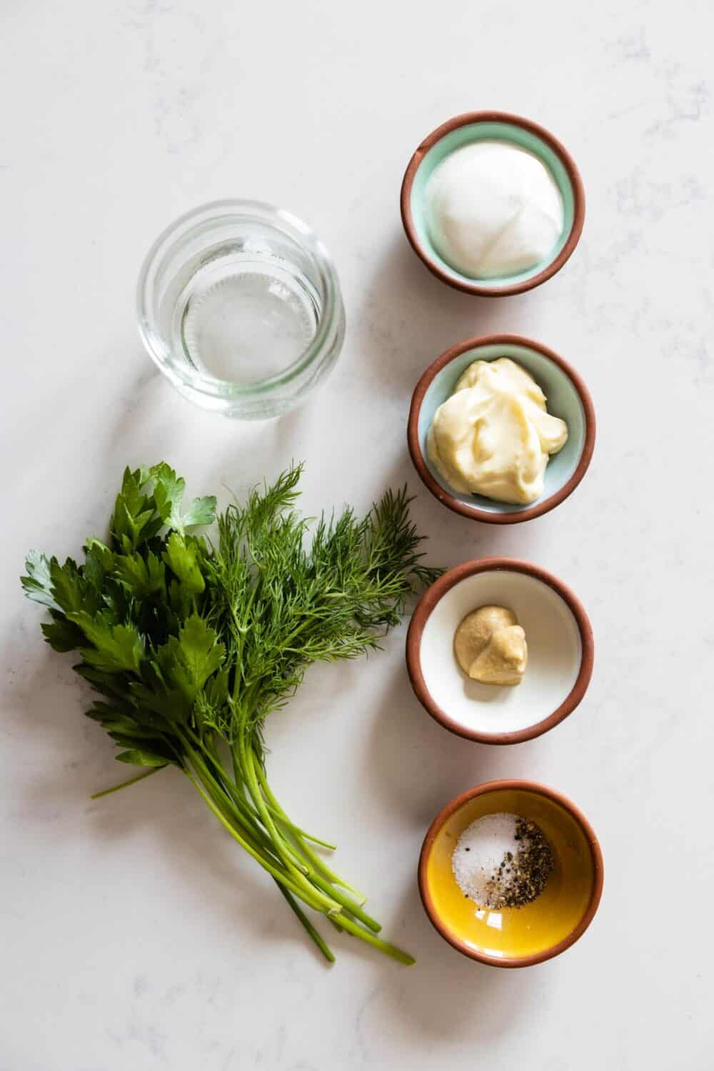 Ingredients for Greek Yogurt Herb Dressing laid out on a kitchen counter.