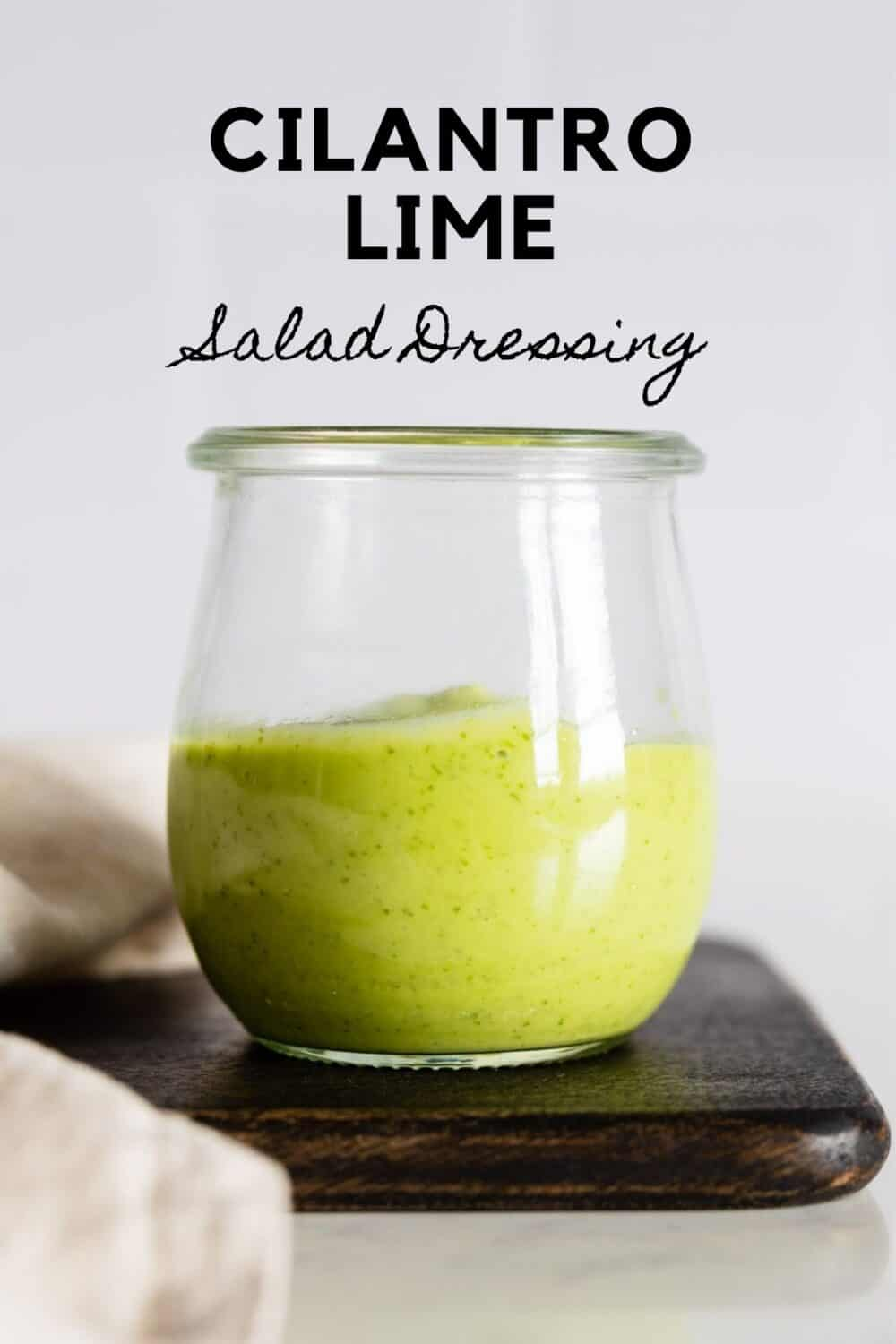 Glass jar with green salad dressing with title reading: Cilantro Lime Salad Dressing.