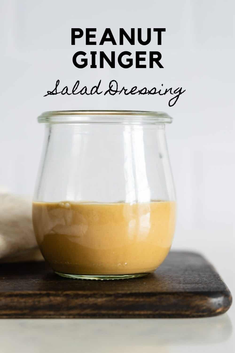Glass jar with light brown salad dressing with title reading: Peanut Ginger Salad Dressing.