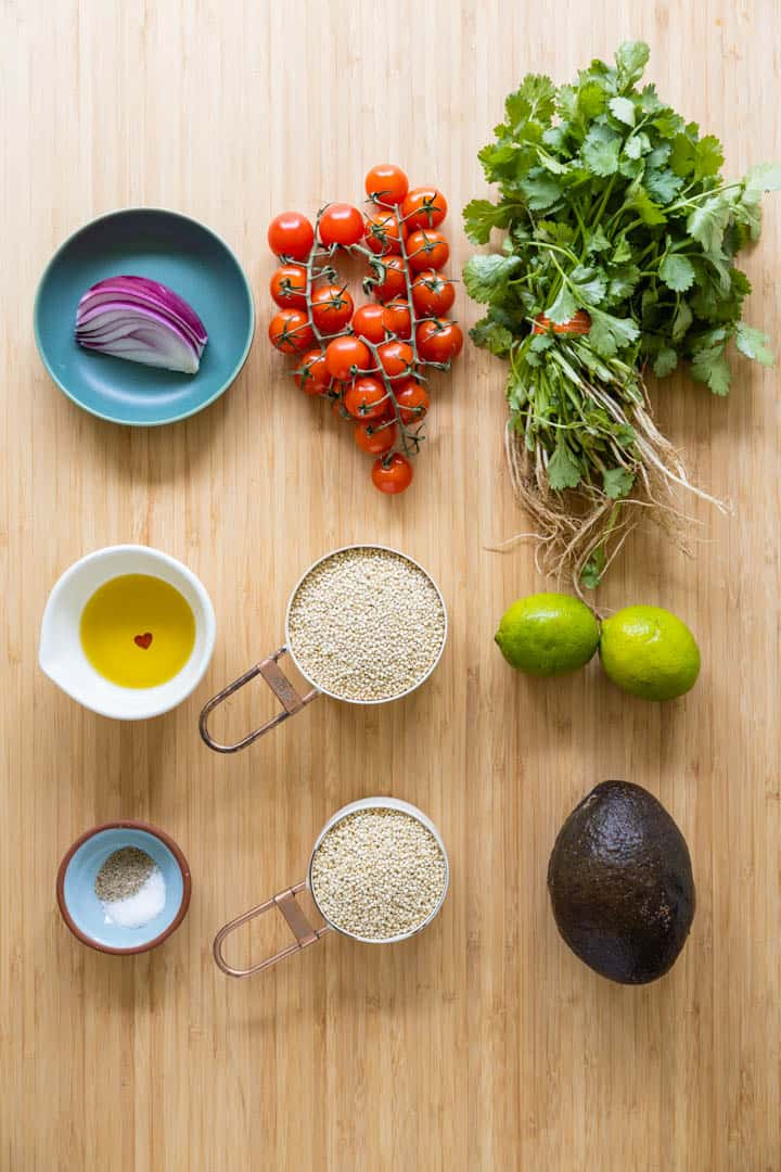 Ingredients for quinoa salad laid out on a kitchen counter.