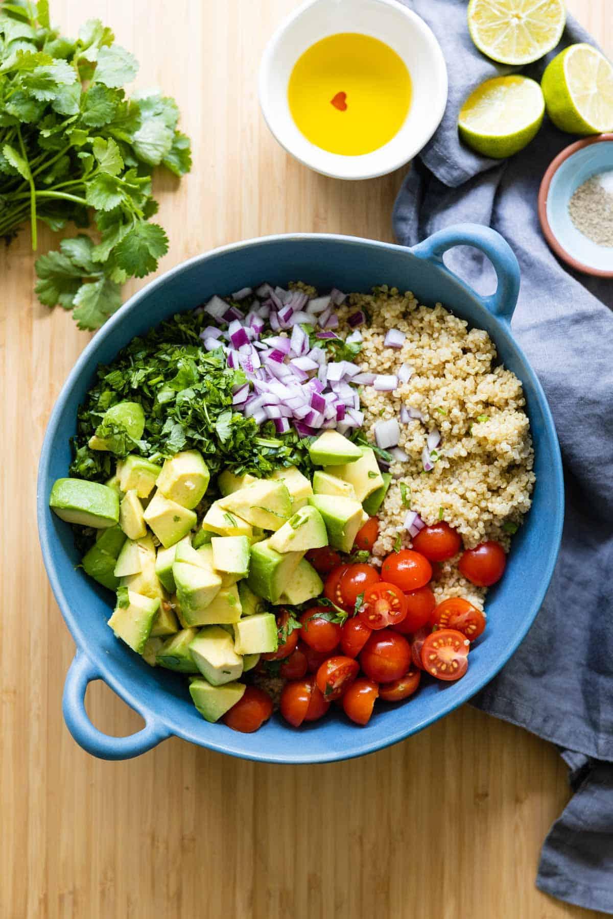 quinoa, avocado, cherry tomatoes, cilantro and red onion in a blue salad bowl.
