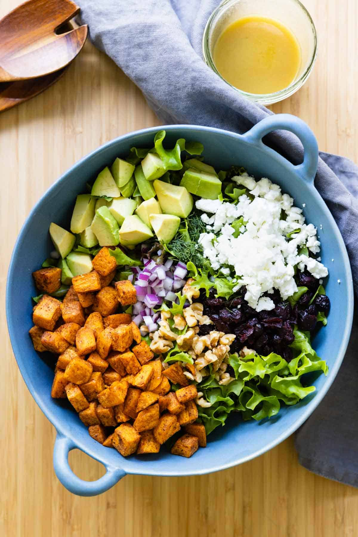 Lettuce, roasted sweet potato, avocado, onion, feta, cranberries in a blue salad bowl, dressing on the side.