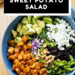 Lettuce, roasted sweet potato, avocado, onion, feta, cranberries in a blue salad bowl, dressing on the side with text overlay for Pinterest.